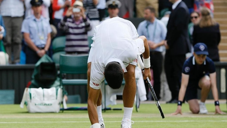 Novak Djokovic of Serbia touches the ground after winning against the Marin Cilic of Croatia after winning the men's quarterfinal singles match at the All England Lawn Tennis Championships in Wimbledon, London, Wednesday July 8, 2015. Djokovic won 6-4, 6-4, 6-4. (AP Photo/Kirsty Wigglesworth)