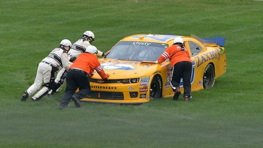 John Wes Townley (25) is assisted by NASCAR safety crews after getting stuck in the soft grass in the infield during the NASCAR Xfinity series auto race at Kentucky Speedway in Sparta, Ky., Friday, July 10, 2015. (AP Photo/Timothy D. Easley)