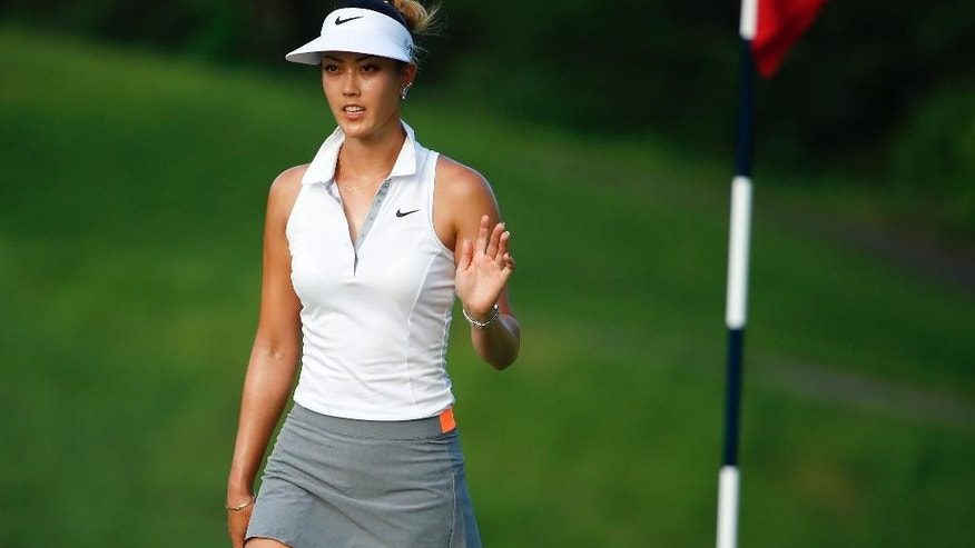 Michelle Wie waves to golf fans as she approaches the eighth green during the second round of the U.S. Women's Open golf tournament at Lancaster Country Club, Friday, July 10, 2015 in Lancaster, Pa. (AP Photo/Gene J. Puskar)