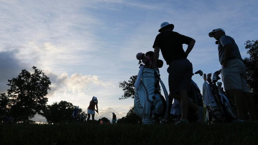 Caddies talk as golfers warm up before play resumed in the first round of the U.S. Women's Open golf tournament at Lancaster Country Club, Friday morning, July 10, 2015, in Lancaster, Pa. Play was suspended the day before after a storm packing high winds, lightning and heavy rain pounded the area. (AP Photo/Frank Franklin II)