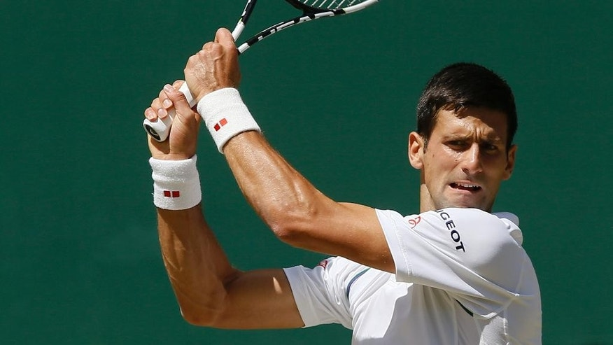 Novak Djokovic of Serbia returns a shot to Richard Gasquet of France during the men's singles semifinal match at the All England Lawn Tennis Championships in Wimbledon, London, Friday July 10, 2015. (AP Photo/Kirsty Wigglesworth)