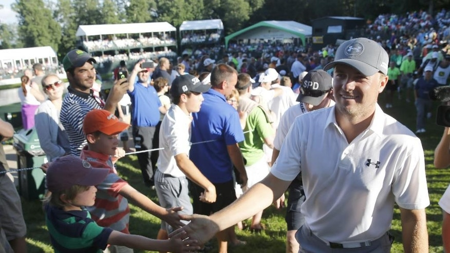Jordan Spieth, right, celebrates with fans after finishing the third round of the John Deere Classic golf tournament Saturday, July 11, 2015, in Silvis, Ill. (AP Photo/Charles Rex Arbogast)
