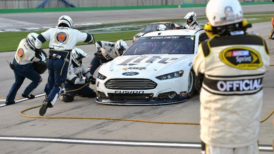 A NASCAR race official watches as the crew of Brad Keselowski performs a pit stop during the NASCAR Sprint Cup auto race at Kentucky Speedway in Sparta, Ky., Saturday, July 11, 2015. (AP Photo/Timothy D. Easley)