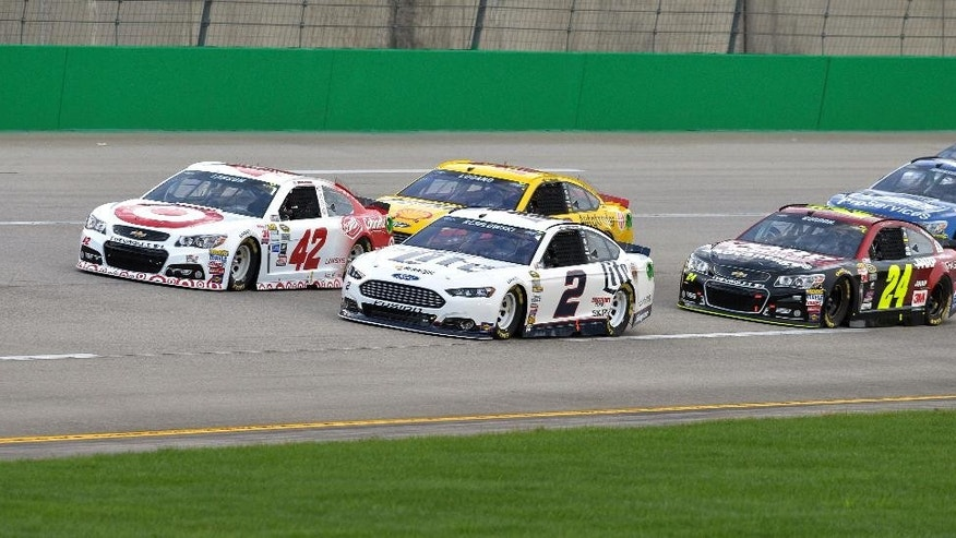 Kyle Larson (42), Brad Keselowsi (2), Joey Logano and Jeff Gordon (24) lead the pack into Turn 1 at the start of the NASCAR Sprint Cup auto race at Kentucky Speedway in Sparta, Ky., Saturday, July 11, 2015. (AP Photo/Timothy D. Easley)