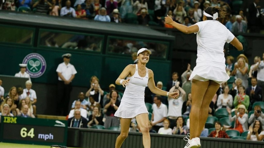 Martina Hingis of Switzerland, left, and Sania Mirza of India celebrate winning the women's doubles final against Ekaterina Makarova of Russia and Elena Vesnina of Russia at the All England Lawn Tennis Championships in Wimbledon, London, Saturday July 11, 2015. (AP Photo/Kirsty Wigglesworth)