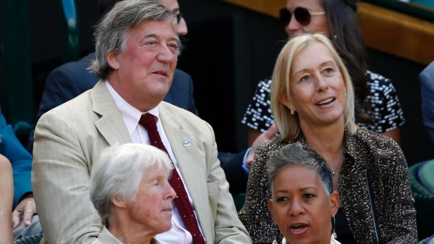 British comedian and actor Stephen Fry, centre left, sits with Former Wimbledon champion Martina Navratilova in the Royal Box on Centre Court, ahead of the women's semifinal matches, at the All England Lawn Tennis Championships in Wimbledon, London, Thursday July 9, 2015. (AP Photo/Alastair Grant)