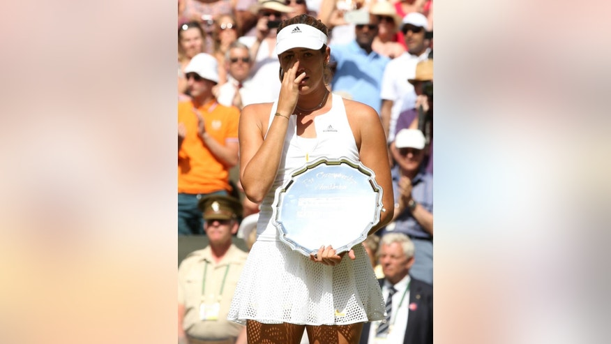 Garbine Muguruza of Spain cries as she holds the runners up trophy during the trophy ceremony after losing to Serena Williams of the United States, at the All England Lawn Tennis Championships in Wimbledon, London, Saturday July 11, 2015. (Sean Dempsey/Pool Photo via AP)