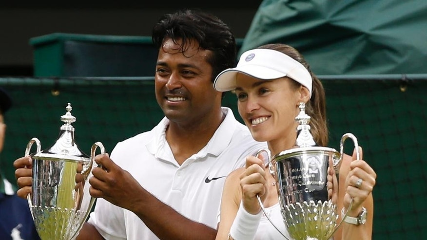 Leander Paes of India, left, and Martina Hingis of Switzerland hold up the trophies after winning the mixed doubles final against Alexander Peya of Austria and Timea Babos of Hungary at the All England Lawn Tennis Championships in Wimbledon, London, Sunday July 12, 2015. (AP Photo/Alastair Grant)