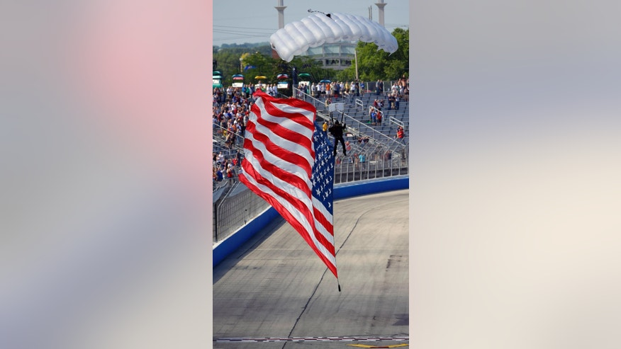 A United States flag, carried by a sky diver, arrives at the start/finish line at the IndyCar Series race at the Milwaukee Mile in West Allis, Wis., Sunday, July 12, 2015. (AP Photo/Jeffrey Phelps)