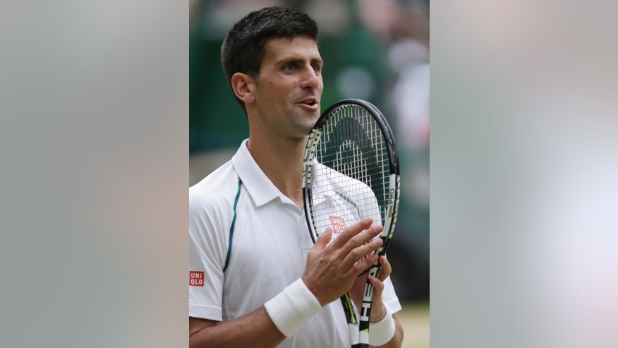 Novak Djokovic of Serbia celebrates winning a point against Roger Federer of Switzerland during the men's singles final at the All England Lawn Tennis Championships in Wimbledon, London, Sunday July 12, 2015. (AP Photo/Pavel Golovkin)