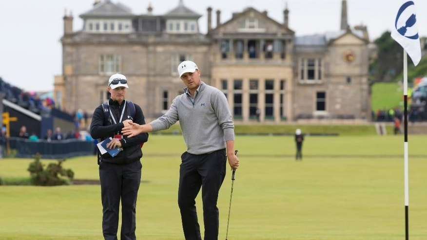 With the clubhouse in the background Jordan Spieth of the United States reacts after playing a shot on the first green during a practice round at St Andrews Golf Club prior to the start of the British Open Golf Championship, in St. Andrews, Scotland, Monday, July 13, 2015. (AP Photo/Jon Super)