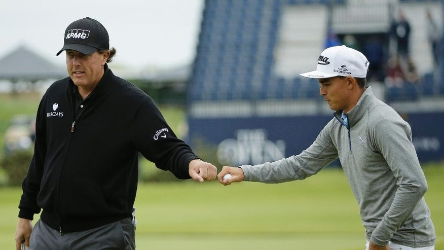 United States' Rickie Fowler, right, bumps his fist with United States' Phil Mickelson after Mickelson saved par after taking a shot off a road alongside the 17th hole during a practice round at the British Open Golf Championship at the Old Course, St. Andrews, Scotland, Tuesday, July 14, 2015. (AP Photo/David J. Phillip)