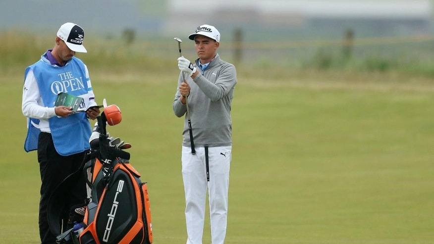 United States' Rickie Fowler inspects a club before taking a shot on the seventh hole during a practice round at the British Open Golf Championship at the Old Course, St. Andrews, Scotland, Tuesday, July 14, 2015. (AP Photo/Peter Morrison)