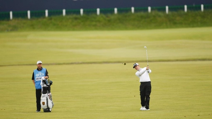 South Africa's Louis Oosthuizen, right, plays his second shot on the 1st hole at the Old Course, St Andrews, Scotland, Monday, July 13, 2015.   Louis Oosthuizen played a practice round ahead of the 2015 Open Golf Championship that is due to take place at St. Andrews July16-19.  (AP Photo/Peter Morrison)