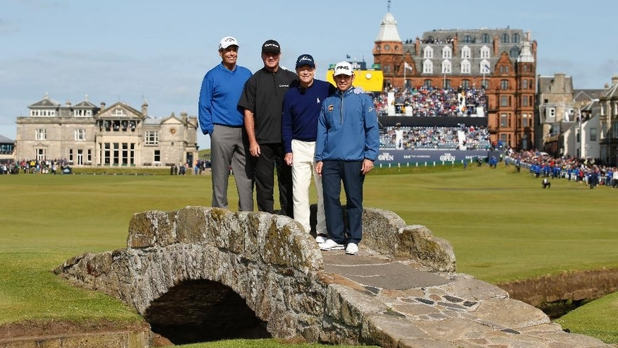 From left, Australia's Ian Baker-Finch, United States' Todd Hamilton, United States' Tom Watson, and South Africa's Louis Oosthuizenduring pose for a photograph on Swilcan Bridge during a special Champion Golfers' challenge at the British Open Golf Championship at the Old Course, St. Andrews, Scotland, Wednesday, July 15, 2015. (AP Photo/Jon Super)