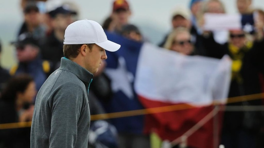 United States' Jordan Spieth walks past a spectator holding the flag of Texas on the 13th hole during the first round of the British Open Golf Championship at the Old Course, St. Andrews, Scotland, Thursday, July 16, 2015. (AP Photo/David J. Phillip)