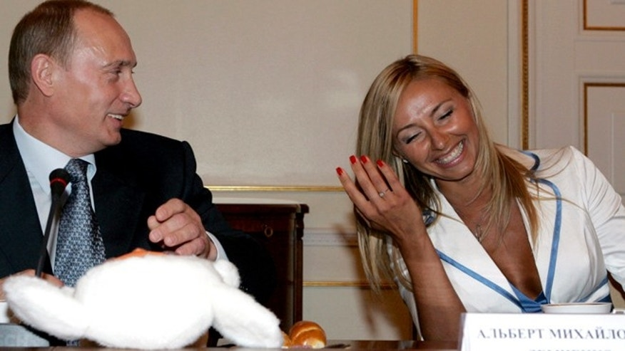 In this Sunday, July 1, 2007 file photo President Vladimir Putin shares a light moment with figure skater Olympic champion Tatiana Navka during a meeting with some of Russia's most renowned and glamorous sports stars in his Novo-Ogaryovo residence outside Moscow, Russia.