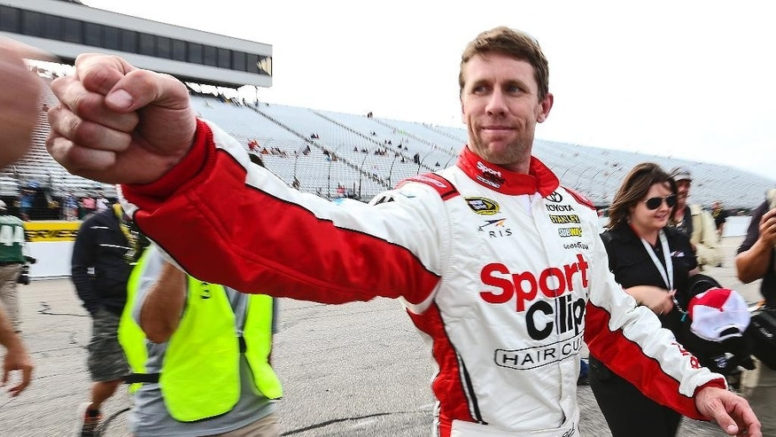 Carl Edwards fist-bumps after winning the pole position qualifying for Sunday's NASCAR Sprint Cup series auto race at New Hampshire Motor Speedway in Loudon, N.H., Friday, July 17, 2015. (AP Photo/Cheryl Senter)