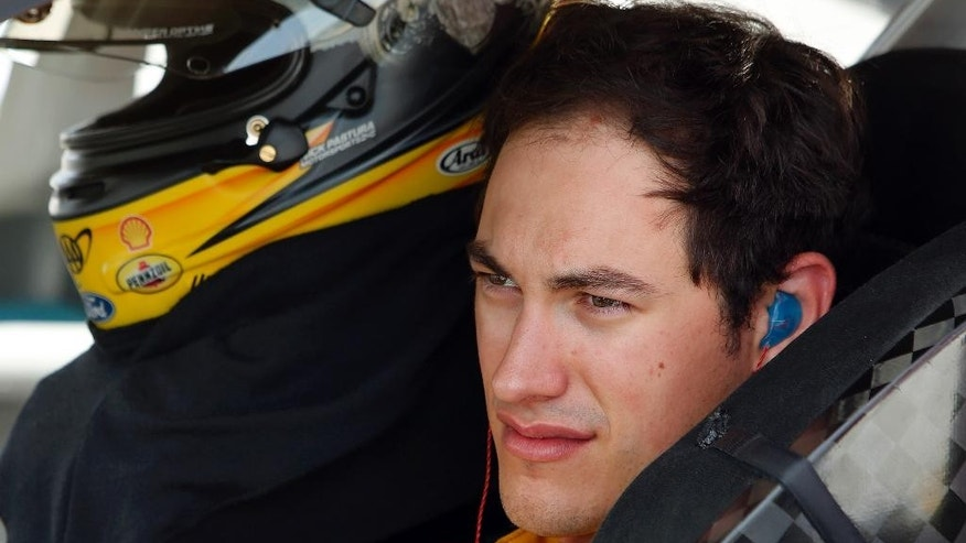 Joey Logano sits in his car as he waits for qualifying to begin for Sunday's NASCAR Sprint Cup series auto race at New Hampshire Motor Speedway, Friday, July 17, 2015, in Loudon,NH (AP Photo/Jim Cole)