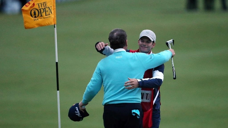 United States' Tom Watson embraces his caddy Michael Watson after finishing on the 18th green during the second round of the British Open Golf Championship at the Old Course, St. Andrews, Scotland, Friday, July 17, 2015. (AP Photo/Peter Morrison)