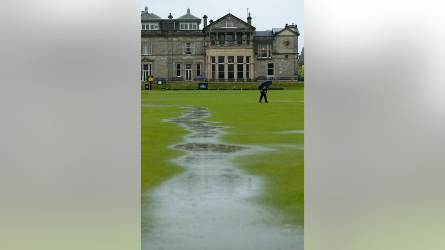 A photographer walks on hole one as pools of water collect after play was suspended due to rain during the second round of the British Open Golf Championship at the Old Course, St. Andrews, Scotland, Friday, July 17, 2015. (AP Photo/David J. Phillip)