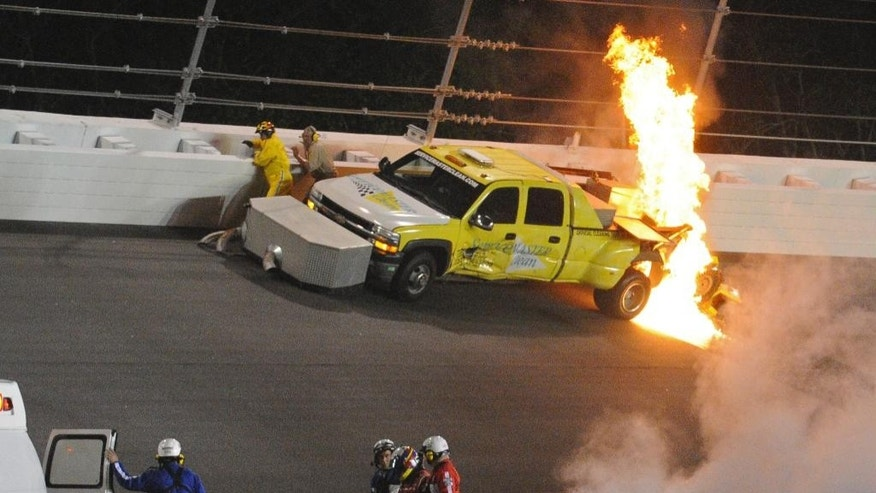 FILE - In this Feb. 27, 2012, file photo, emergency personnel walk with Juan Pablo Montoya, of Colombia, to an ambulance after his car struck a jet dryer during a caution period in the NASCAR Daytona 500 auto race at Daytona International Speedway in Daytona Beach, Fla. The fuel in the dryer began burning. Michigan International Speedway employee Duane Barnes, who survived the 2012 explosion and fire, has died. He was 55. The Brown-Van Hemert Funeral Home says Barnes died at his home in Addison, Mich., on Tuesday, July 14, 2015. He spent 27 years at the speedway in Brooklyn. Barnes was driving the jet dryer when something broke on Montoya's car and sent it careening into Barnes' truck. (AP Photo/Rob Sweeten, File)