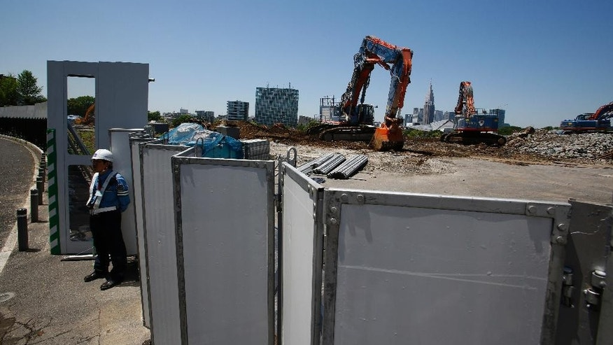 """FILE - In this May 13, 2015 file photo, a guard stands by Japan's National Stadium which is dismantled for the renovation for the 2020 Tokyo Olympics, in Tokyo. Japan's government is on the defensive as criticism mounts over the spiraling cost to build the main stadium for the 2020 Summer Games. Newly appointed Olympics Minister Toshiaki Endo acknowledged on Tuesday, July 14, 2015 that the latest estimate of 252 billion yen ($2 billion) represents a """"substantial increase"""" from the initial estimate of 162.5 billion yen. (AP Photo/Shizuo Kambayashi, File)"""