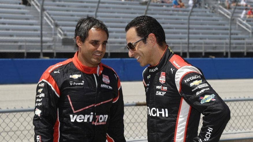 Juan Pablo Montoya, left, and Helio Castroneves wait during qualifying at the IndyCar Series race at the Milwaukee Mile in West Allis, Wis., Sunday, July 12, 2015. (AP Photo/Jeffrey Phelps)