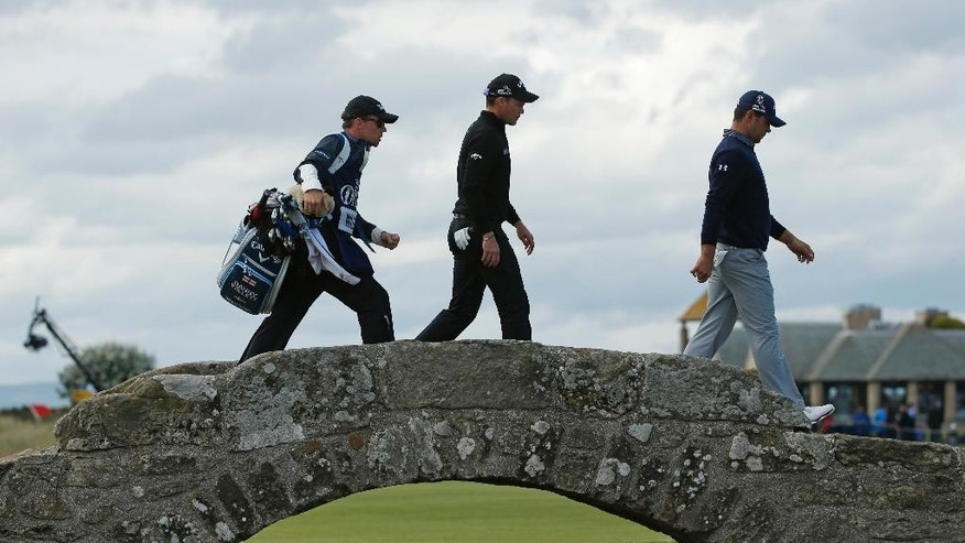 England's Danny Willett, center, and United States' Gary Woodland cross the Swilcan Bridge on the 18th hole during the second round of the British Open Golf Championship at the Old Course, St. Andrews, Scotland, Friday, July 17, 2015. (AP Photo/Jon Super)