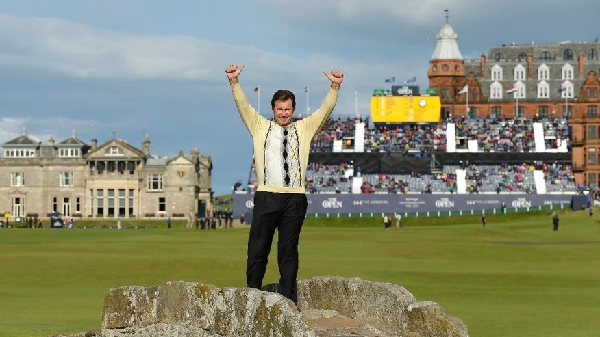 England's Nick Faldo waves as he poses for photographers on the Swilcan Bridge during the second round of the British Open Golf Championship at the Old Course, St. Andrews, Scotland, Friday, July 17, 2015. (AP Photo/David J. Phillip)