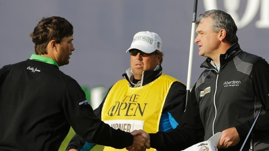 Scotland Paul Lawrie, right, shakes hands with United States' Kevin Kisner after finishing the second round of the British Open Golf Championship at the Old Course, St. Andrews, Scotland, Saturday, July 18, 2015. (AP Photo/David J. Phillip)