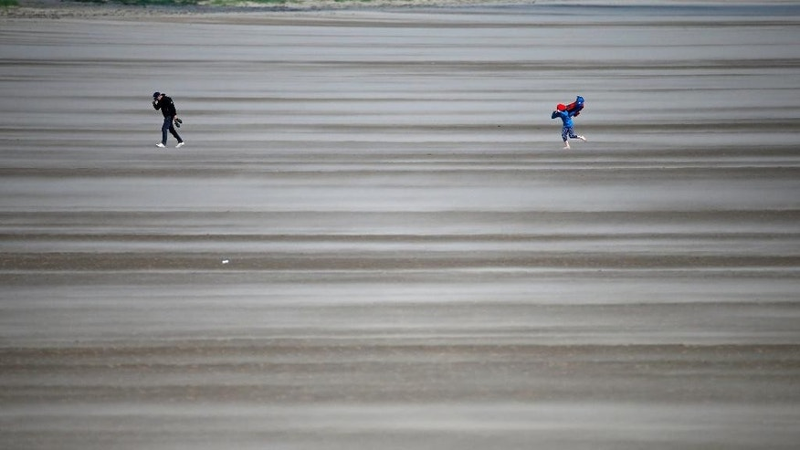 People walk on a windswept beach near the course as high winds suspend play during the second round of the British Open Golf Championship at the Old Course, St. Andrews, Scotland, Saturday, July 18, 2015. (AP Photo/Jon Super)