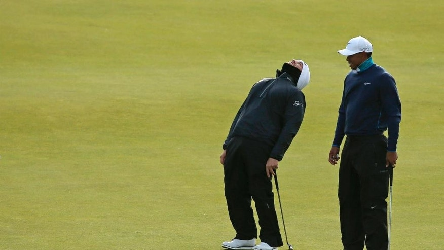 South Africa' Louis Oosthuizen, left, reacts after a putt on the 13th green as United States' Tiger Woods looks on during the second round of the British Open Golf Championship at the Old Course, St. Andrews, Scotland, Saturday, July 18, 2015. (AP Photo/Jon Super)