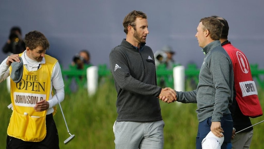 United States' Jordan Spieth, right, shakes hands with United States' Dustin Johnson after finishing their round on the 18th green during the second round of the British Open Golf Championship at the Old Course, St. Andrews, Scotland, Saturday, July 18, 2015. (AP Photo/David J. Phillip)
