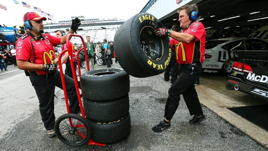 Diver Jamie McMurray's crew handles spent tires removed from his car during practice for Sunday's NASCAR Sprint Cup series auto race at New Hampshire Motor Speedway, in Loudon, N.H., Saturday, July 18, 2015  (AP Photo/Cheryl Senter)