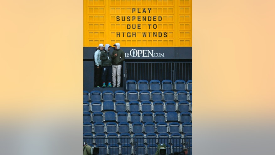 A scoreboard near the 18th hole announces that play has been suspended due to high winds during the second round of the British Open Golf Championship at the Old Course, St. Andrews, Scotland, Saturday, July 18, 2015. Play was suspended on Saturday as high winds caused players golf balls to move on some greens.  (AP Photo/Jon Super)