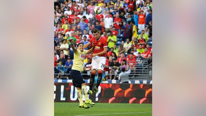 Manchester United's Morgan Schneiderlin (28) heads in a goal past Club America's Javier Guemez, left, in the first half of an international friendly soccer match, Friday, July 17, 2015, in Seattle. (AP Photo/Ted S. Warren)