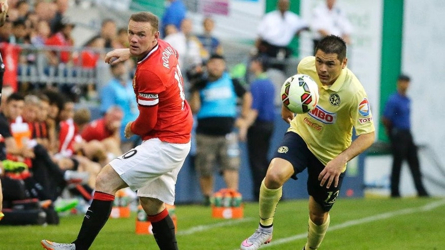 Manchester United's Wayne Rooney, left, looks back asClub America's Pablo Cesar Aguilar moves the ball during the first half of an international friendly soccer match, Friday, July 17, 2015, in Seattle. (AP Photo/Ted S. Warren)
