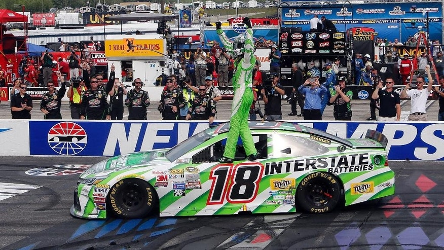 Kyle Busch celebrates at the finish line After winning the the NASCAR Sprint Cup series auto race at New Hampshire Motor Speedway Sunday, July 19, 2015, in Loudon, N.H. (AP Photo/Jim Cole)