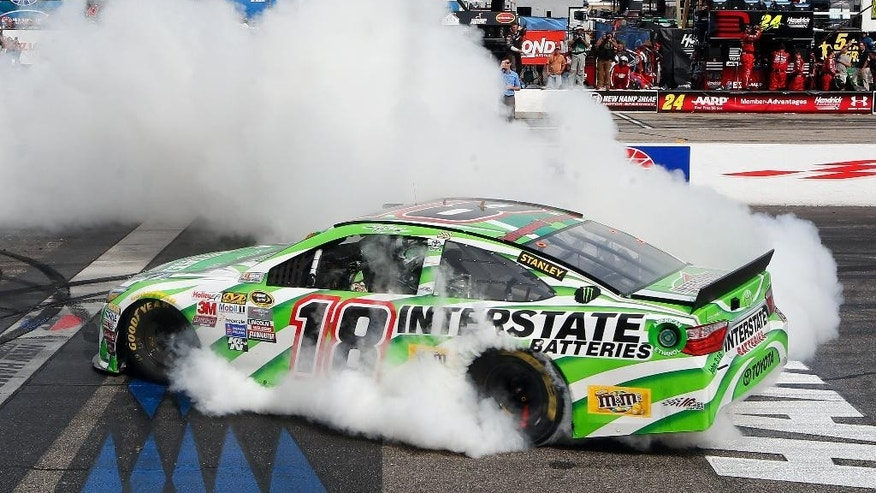 Kyle Busch burns out after winning the NASCAR Sprint Cup series auto race at New Hampshire Motor Speedway Sunday, July 19, 2015, in Loudon, N.H. (AP Photo/Jim Cole)