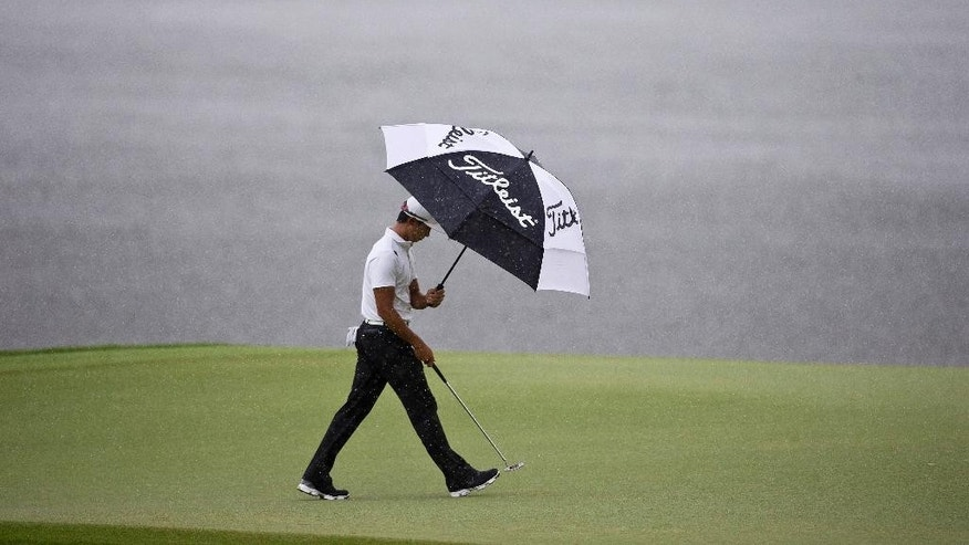 Whee Kim, of South Korea, walks in the rain toward the third hole during the final round of the Barbasol Championship golf tournament Sunday, July 19, 2015, in Opelika, Ala. (AP Photo/Butch Dill)