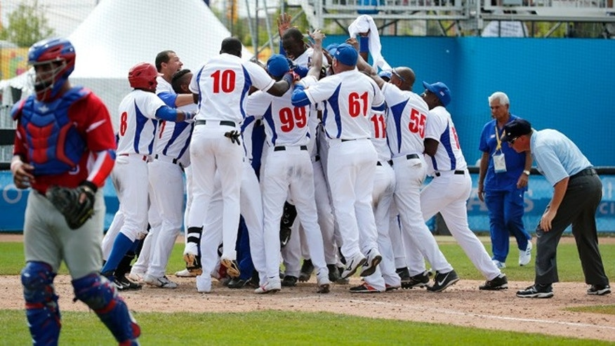 Cuba's Jose Garcia, top center, is mobbed by teammates after hitting a walk off home run off Puerto Rico pitcher Raul Rivera in the ninth inning of the bronze medal baseball game at the Pan Am Games, Sunday, July 19, 2015, in Ajax, Ontario. Cuba won 7-6. (AP Photo/Julio Cortez)