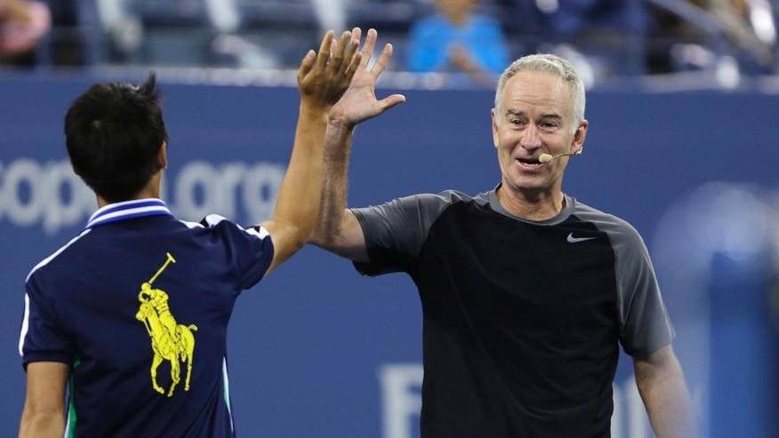 FILE - In this Sept. 4, 2014, file photo, John McEnroe high-fives a ball boy during an exhibition match prior to the quarterfinal between Roger Federer and Gael Monfils at the U.S. Open tennis tournament  in New York. John McEnroe says he's almost done playing competitive tennis. The 56-year-old Hall of Famer plans to play an exhibition match against Jim Courier next month in New Haven. That will be part of a Legends Event designed to increase attendance at the Connecticut Open, the last women's tournament before the U.S. Open. McEnroe told reporters on a conference call Tuesday, July 21, 2015,  the match is probably the last chance fans in Connecticut will have to see him play competitively. (AP Photo/Charles Krupa, File)