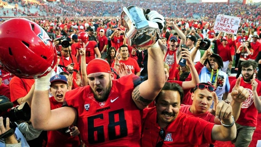 Nov 28, 2014; Tucson, AZ, USA; Arizona Wildcats offensive lineman Mickey Baucus (68) hoists the territorial cup in celebration after beating the Arizona State Sun Devils 42-35 at Arizona Stadium. Mandatory Credit: Matt Kartozian-USA TODAY Sports