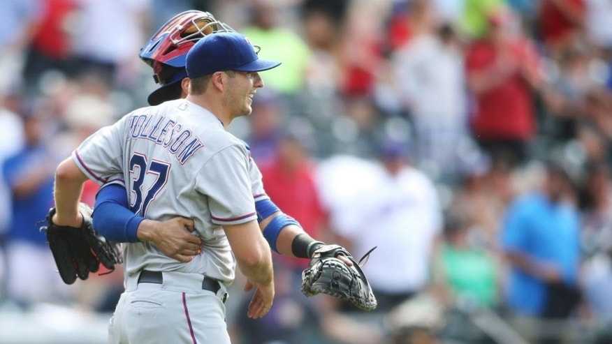 Jul 22, 2015; Denver, CO, USA; Texas Rangers relief pitcher Shawn Tolleson (37) and catcher Robinson Chirinos (61) celebrate after defeating the Colorado Rockies 10-8 at Coors Field. Mandatory Credit: Chris Humphreys-USA TODAY Sports