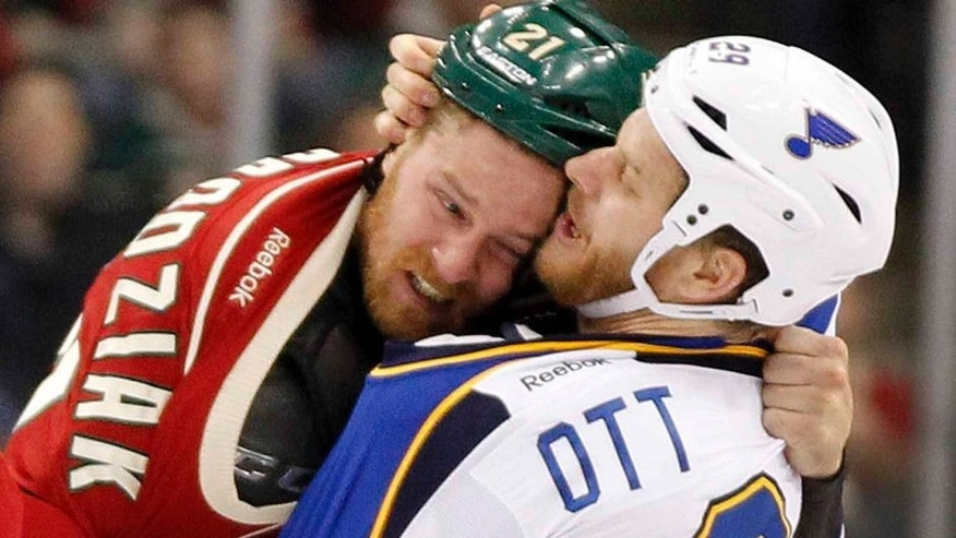 Minnesota Wild center Kyle Brodziak (left) and St. Louis Blues center Steve Ott fight during the first period.