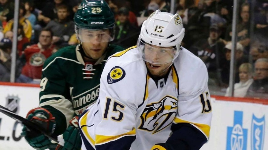 Nashville Predators center Craig Smith (right) controls the puck in front of Minnesota Wild right wing Jason Pominville during the second period.