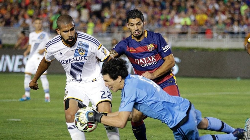 Los Angeles Galaxy goalkeeper Brian Rowe, front, makes a save in front of Galaxy's Leonardo, left, and FC Barcelona's Luis Suarez during the first half of an International Champions Cup soccer match Tuesday, July 21, 2015, in Pasadena, Calif. (AP Photo/Jae C. Hong)