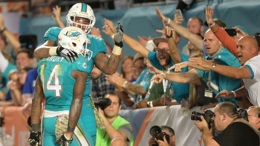 Nov 13, 2014; Miami Gardens, FL, USA; Miami Dolphins guard Mike Pouncey (51) celebrates after wide receiver Jarvis Landry (14) scored a touchdown against the Buffalo Bills during the second half at Sun Life Stadium. The Dolphins won 22-9. Mandatory Credit: Steve Mitchell-USA TODAY Sports