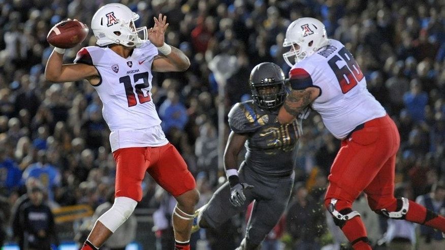 Nov 1, 2014; Pasadena, CA, USA; Arizona Wildcats quarterback Anu Solomon (12) passes the ball as offensive lineman Mickey Baucus (68) blocks UCLA Bruins linebacker Myles Jack (30) during the first quarter at Rose Bowl. Mandatory Credit: Jake Roth-USA TODAY Sports